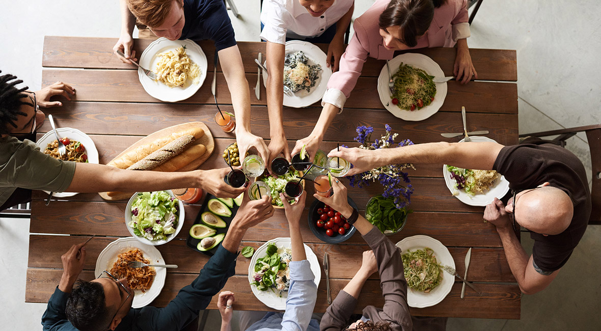 Overhead view of eight people making a toast with drinks around wood dining table with food.