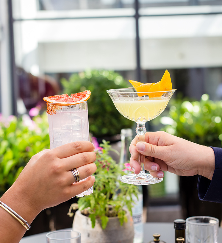 Closeup of two people making a toast holding finely cut glassware filled with colorful drinks and garnished with fruit.