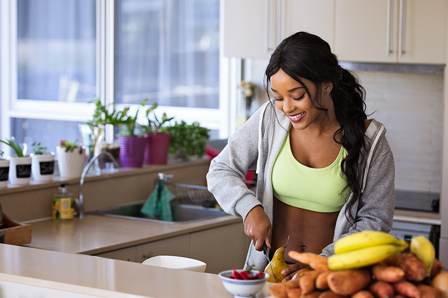 Person in sweatshirt and sports bra smiles while slicing fruit in brightly lit apartment kitchen.