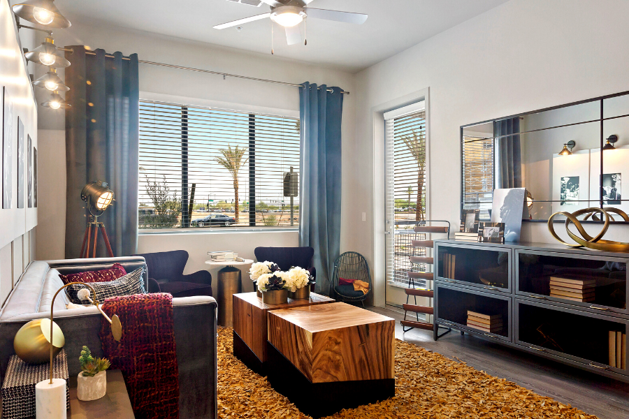 Living room with large windows, patio door, faux wood blinds, and hardwood floors.